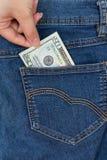A mão obtém o dinheiro do bolso de brim fotografia de stock royalty free