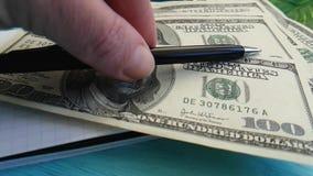 A mão põe o escritório dos dólares da pena do bloco de notas filme