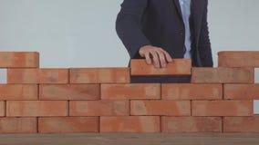 A mão põe o tijolo na parede video estoque