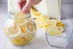 A mão põe uma fatia de limão em uma lata fotografia de stock