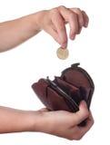 A mão põe uma moeda na bolsa Imagens de Stock Royalty Free