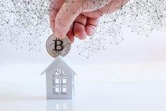A mão põe uma moeda na casa imagem de stock