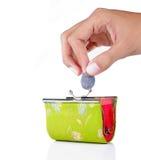 A mão põr a moeda na carteira Imagem de Stock Royalty Free