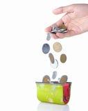 A mão põr a moeda na carteira Foto de Stock