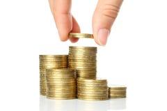 A mão põr moedas à pilha de moedas Foto de Stock