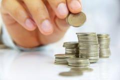 A mão pôr a moeda à pilha Fotografia de Stock Royalty Free