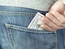A mão pôs dólares no bolso das calças de brim Fotos de Stock