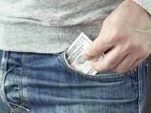 A mão pôs dólares no bolso das calças de brim Foto de Stock Royalty Free