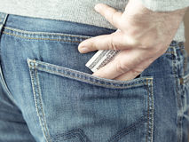 A mão pôs dólares no bolso das calças de brim Imagem de Stock