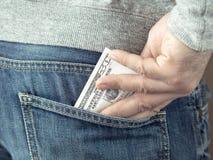 A mão pôs dólares no bolso das calças de brim Imagens de Stock