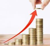 A mão pôs a moeda ao dinheiro Foto de Stock
