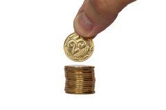 A mão pôs a moeda sobre uma pilha de finança do negócio do valor do dinheiro das moedas Foto de Stock Royalty Free