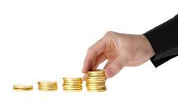 A mão pôs moedas na pilha de moedas Foto de Stock