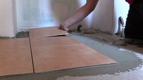 A mão pôs o azulejo sobre o assoalho da colagem do cimento em casa video estoque