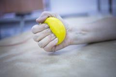 Mão paciente que espreme a bola da fisioterapia Foto de Stock