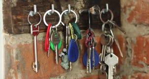A mão pendura em um gancho um grupo de chaves video estoque