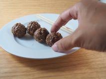 Mão picando - bolas do chocolate de leite Imagem de Stock Royalty Free