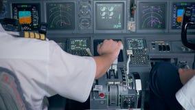 A mão piloto do ` s é posicionada em uma alavanca de regulador de pressão em uma cabina do piloto de aviões filme