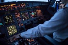 Mão piloto do ` s que acelera no regulador de pressão em um airlineri comercial imagens de stock