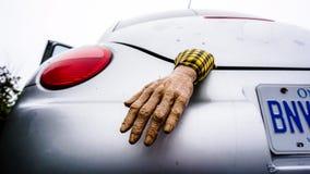 Mão plástica de Dia das Bruxas que sai de um tronco de carro fotos de stock