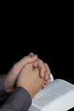Mão Praying com a Bíblia santamente Imagens de Stock