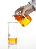 A mão prende a garrafa para fazer uma reacção química Imagens de Stock Royalty Free