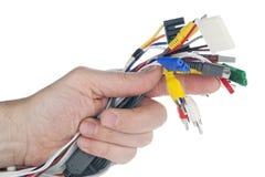 A mão prende o jogo de cabos com conectores fotografia de stock