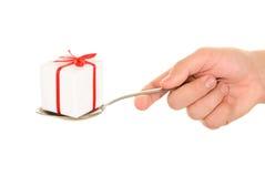 A mão prende o presente no spoo imagens de stock
