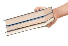 A mão prende três livros imagens de stock