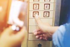 A mão pressiona no botão velho do elevador, botão vermelho fim imagem de stock royalty free