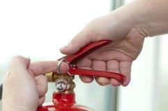A mão pressiona o extintor de incêndio do disparador Imagem de Stock Royalty Free