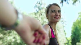 Mão principal do noivo da menina alegre no treinamento da aptidão no parque Siga-me filme