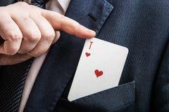 A mão puxa o ás do cartão de corações Imagens de Stock