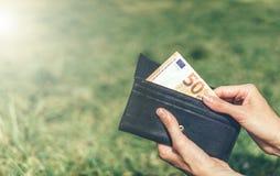 A mão puxa uma conta de 50 euro da carteira fotos de stock royalty free