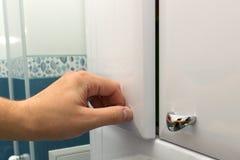 Mão que abre uma porta de gabinete Imagem de Stock Royalty Free