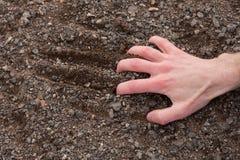 Mão que adere-se a uma terra rochoso Imagens de Stock Royalty Free