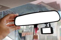 Mão que ajusta o espelho retrovisor e o vídeo do registro da câmera no carro fotos de stock