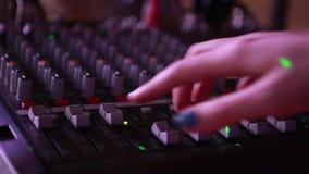 Mão que ajusta o misturador audio vídeos de arquivo