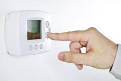 Mão que ajusta o termostato digital Fotos de Stock Royalty Free