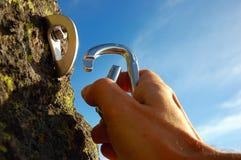 Mão que anexa o carabiner Fotografia de Stock Royalty Free