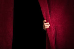 Mão que aparece abaixo da cortina. imagem de stock