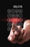 Mão que aponta a calculadora app no fundo preto Imagem de Stock Royalty Free