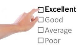 Mão que aponta a excelente no exame da qualidade Imagem de Stock Royalty Free