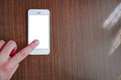 Mão que aponta o dedo no smartphone com tela branca imagem de stock