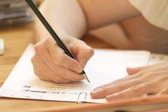 Mão que aprende a rotulação na classe com lápis e Livro Branco fotografia de stock royalty free