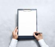 Mão que assina a prancheta vazia com o modelo branco do projeto do papel a4 Fotos de Stock