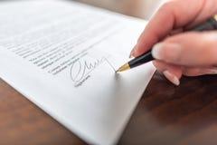 Mão que assina um contrato Fotos de Stock