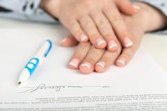 Mão que assina um contrato Imagens de Stock Royalty Free