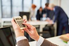 Mão que calcula com calculadora foto de stock