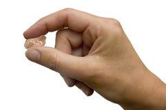Mão que comprime moedas de um centavo Imagens de Stock